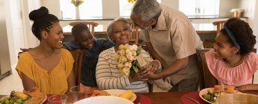 Front view of African American senior man giving a beautiful flower bouquet to his wife surrounded by her daughter and her grandchildren while having meal on dining table at home