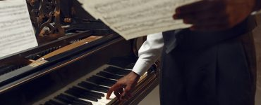Black pianist with music notebook in his hands on the stage with spotlights on background. Negro performer poses at musical instrument before concert