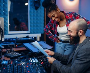 Sound operator and female singer at remote control panel in audio recording studio. Musician at the mixer, professional music mixing
