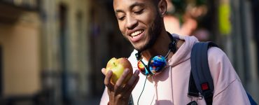 Young black man eating an apple walking down the street. Lifestyle concept.