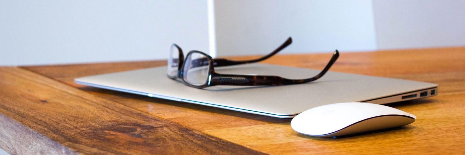 reading glasses on laptop table writer author