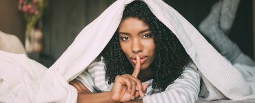 attractive black woman asking for silence with finger on lips on bed